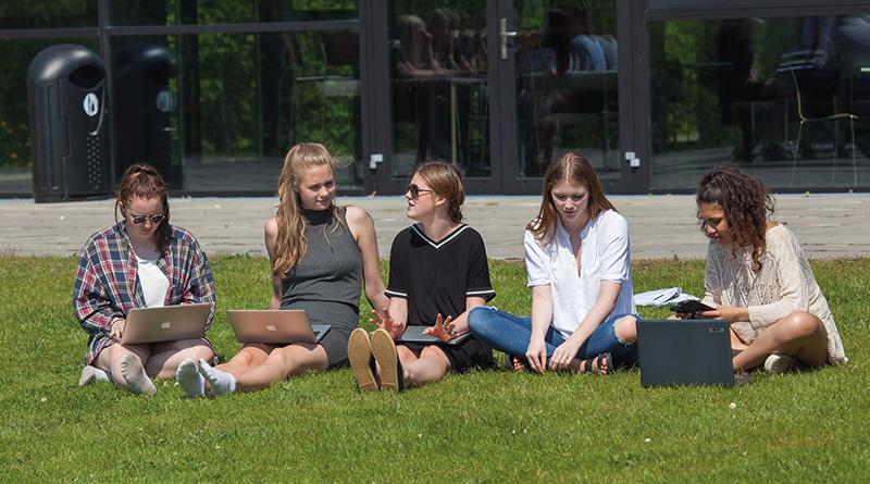 Fem gymnasieelever sidder udenfor